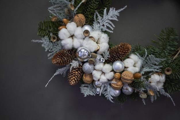Деталь крупным планом рождественский венок из лозы украшен еловыми ветками, елочными шарами и натуральными материалами,