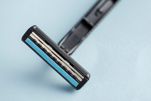 Detail of disposable black razor against blue backdrop