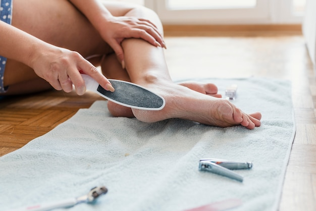 Detail of female feet care. close-up of woman having pedicure to her legs