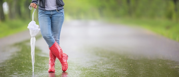 Detail of female legs in rain boots and a closed umbrella standing on the road on a rainy day.