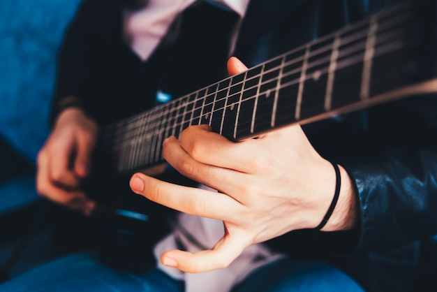 Detail of the fingers of a guitarist playing a chord on an electric guitar.