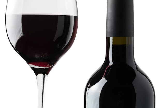 Detail of a glass of red wine next to a bottle on a black background