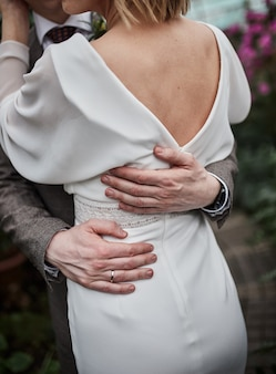 Detail of a groom's hand on the waist of his bride. couple embracing