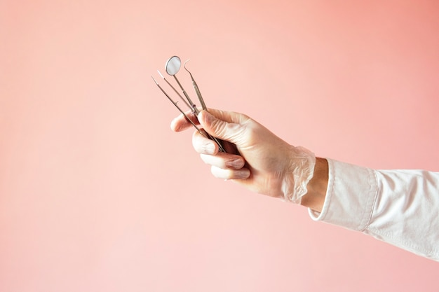 Detail of hand holding dental tools in dental clinic, with pink background. dental clinic.