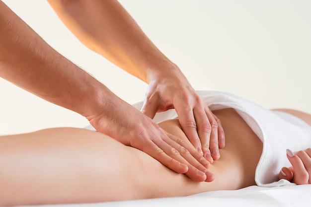 Dettaglio delle mani che massaggiano il muscolo del polpaccio umano.