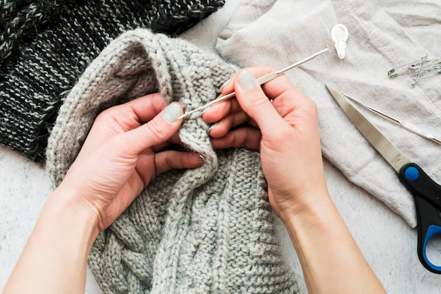 Detail of the hands of a woman crocheting with crochet needle