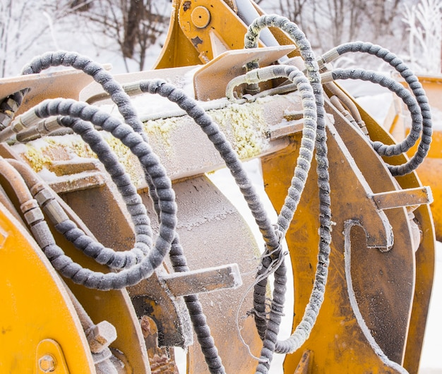 Detail of hoses with dirt and frost of an excavator
