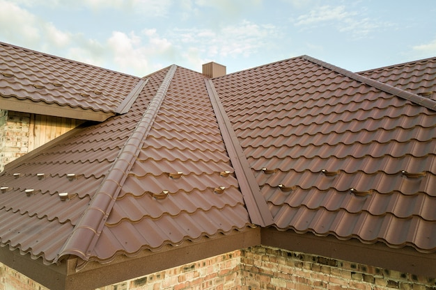 Detail of house roof structure covered with brown metal tile sheets.
