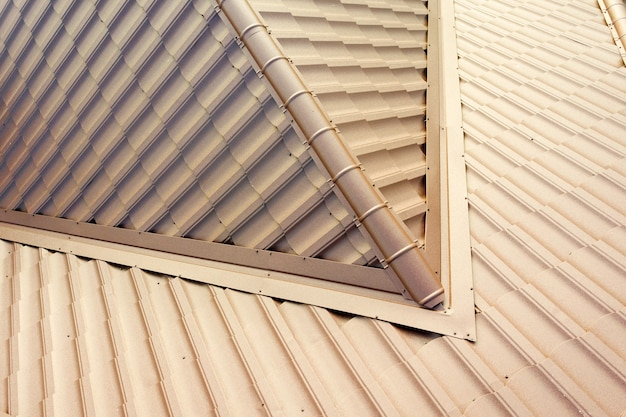 Detail of a house roof surface covered with brown metal tile sheets.