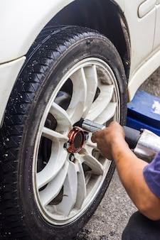 ガレージの背景がぼやけている、ツール、車のタイヤを交換するメカニックの手の詳細画像。手持ちの動きでソフトフォーカス。