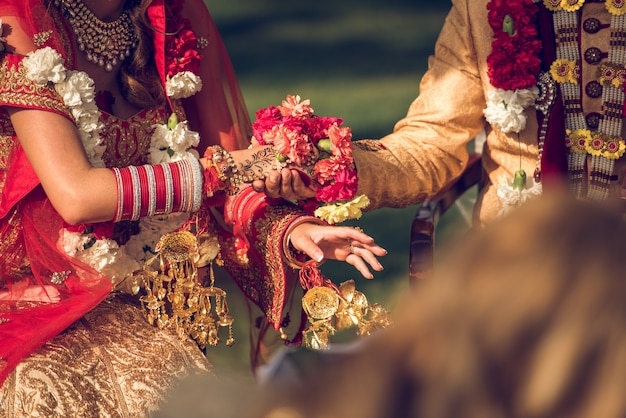 Detail of an indian wedding with elegant dresses, carnations and gold jewels. tradition and travel concept