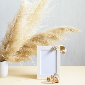 Detail of interior decoration with natural plant phragmites and wooden photo frame