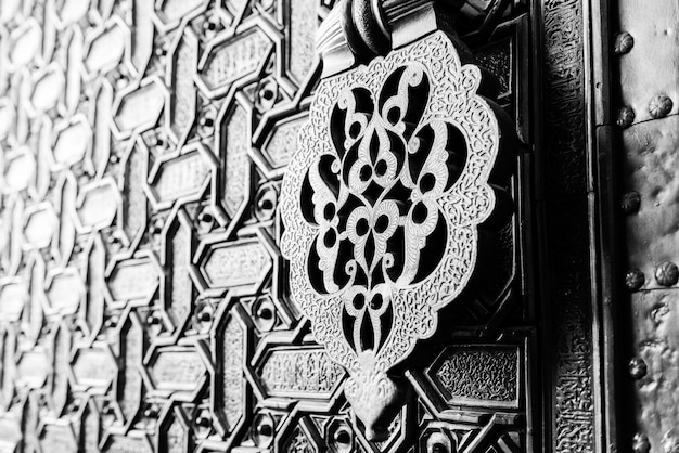 Detail of an islamic door knocker and ornaments outside one of the main entrance gates to the cathedral of seville, spain.