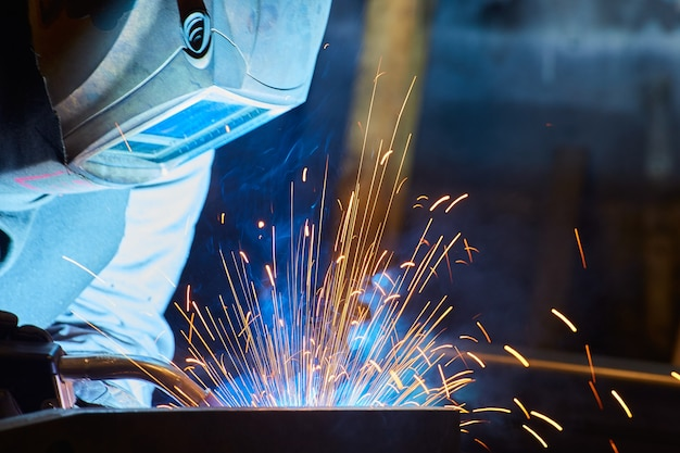 Detail of metal worker welding with welding mask sparks flying blue and orange