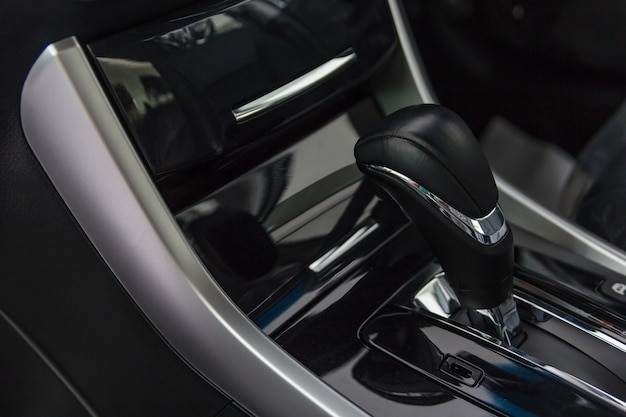 Detail of modern car interior focus on gear stick, automatic transmission in luxury car