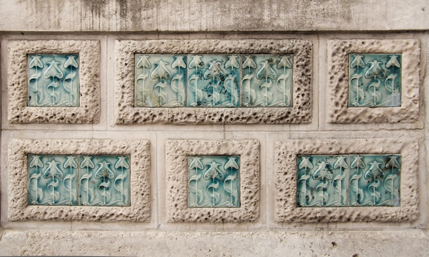Detail of modernist flowers carving in stone wall rectangles