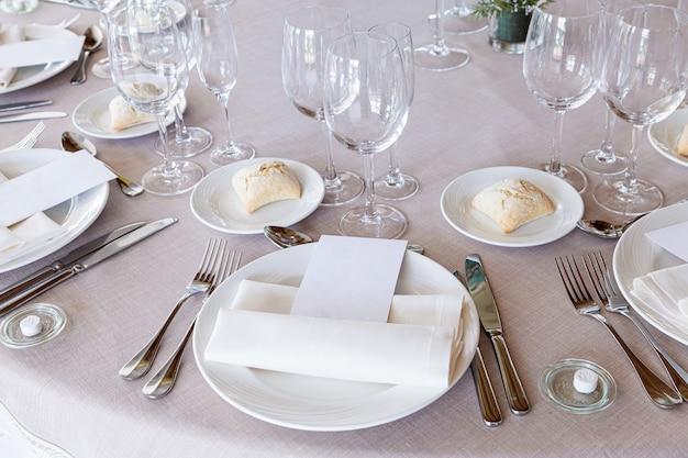 食器、カトラリー、ワイングラスと空白のメニュー用紙を備えた美しい結婚式のテーブルの詳細