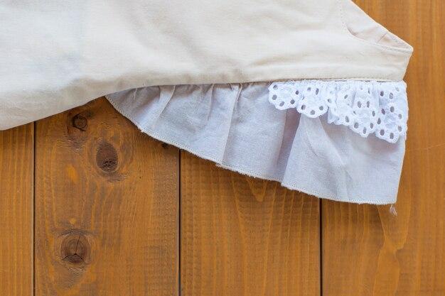 베이지색 어린이 드레스 클로즈업, 드레스 날개, 레이스, 면, 위쪽 전망의 세부 사항.