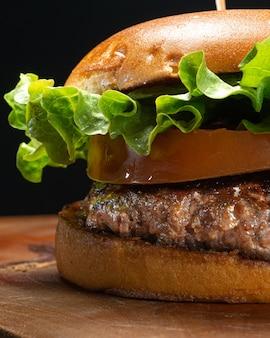 黒の背景に素朴な木で提供されるスライスされたトマトとレタスのハンバーガーの詳細。