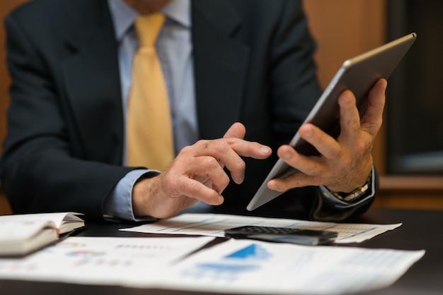 Деталь бизнесмена, используя его планшет в офисе