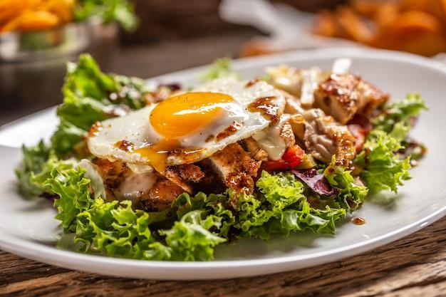 접시에 계란을 위로 써니 사이드와 치킨 샐러드의 세부 사항.