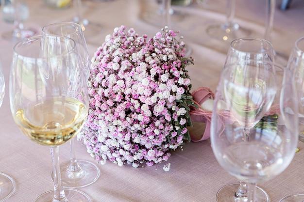 結婚式のテーブルにピンクの花の繊細なブライダルブーケとその周りに白ワインのグラスの詳細