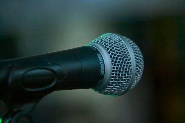 背景を完全にぼかした状態で正面(歌手の視点)で撮影した歌唱用マイクのディテール。グラフィカルリソースとして役立ちます。