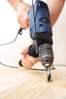 ドリルで天然松の木板を掘削する人の手の詳細。仕事とdiyのコンセプト。
