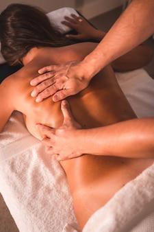 テーブルの上に横たわっている若い女性の理学療法士の背中のマッサージの詳細。理学療法、整骨、リラックスマッサージ、背中の治療のモーションビデオ