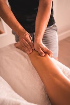 テーブルの上に横たわっている若い女性の左脚の後ろにある理学療法士のマッサージの詳細。理学療法、整骨、リラックスマッサージ、背中の治療のモーションビデオ