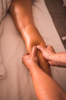 テーブルの上に横たわっている若い女性の右脚の後ろにある理学療法士のマッサージの詳細。理学療法、整骨、リラックスマッサージ、背中の治療のモーションビデオ