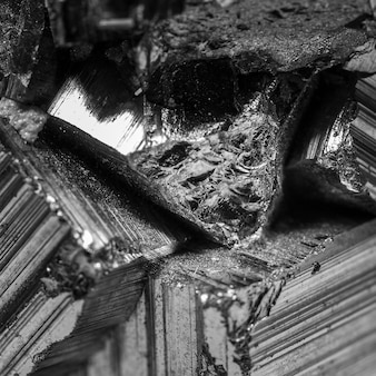 Деталь минерала пирита в черно-белом. пирит - очень распространенный минерал, состоящий из дисульфида железа, который при ударе металлическим предметом дает искры.