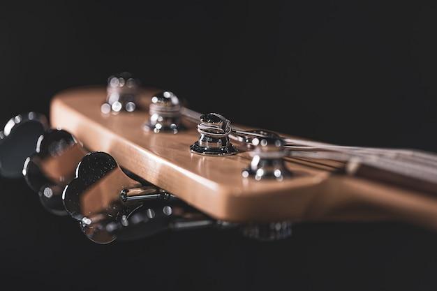 일렉트릭 베이스 기타의 나무 주축에 있는 튜닝 포스트의 세부 사항.