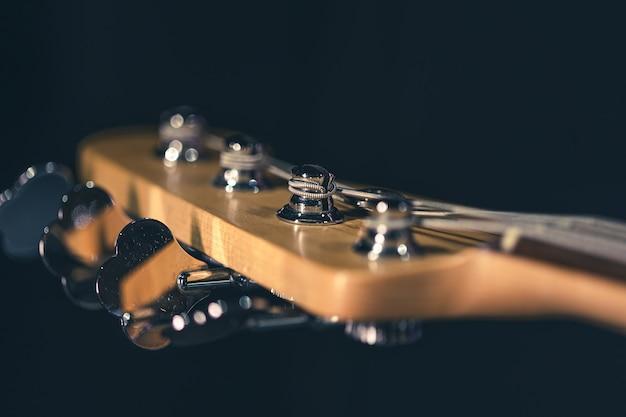 エレクトリックベースギターの木製ヘッドストックのチューニングポストの詳細。