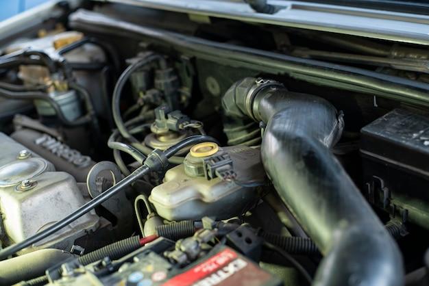 자동차 내부에서 볼 수 있는 기계 부품이 있는 중고 엔진의 세부 사항