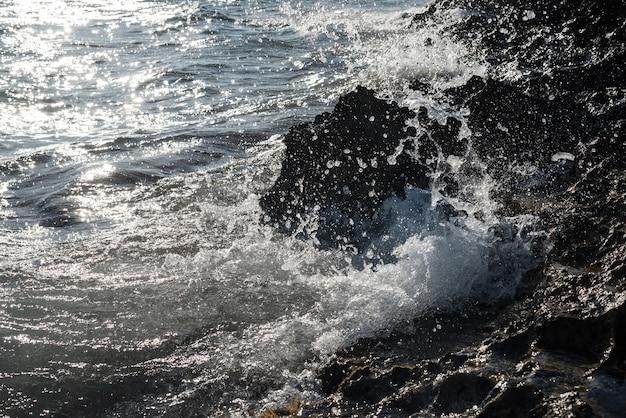 많은 물 방울이 튀는 바위에 대 한 해안에 깨는 파도의 세부 사항. 빠른 셔터 정지 동작.