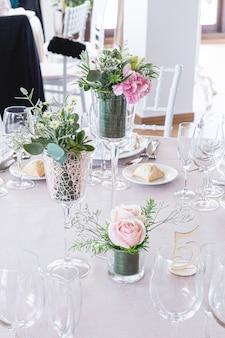 ピンクのバラと緑の葉の花束を飾った結婚式のテーブルの詳細