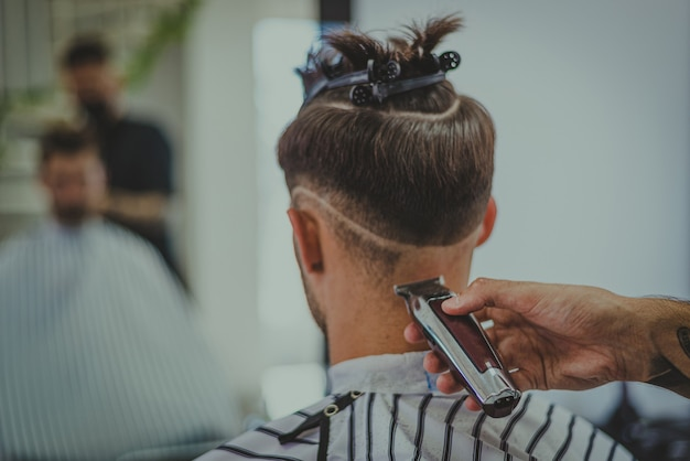 理髪店で若い男のディテールが男の髪を切る