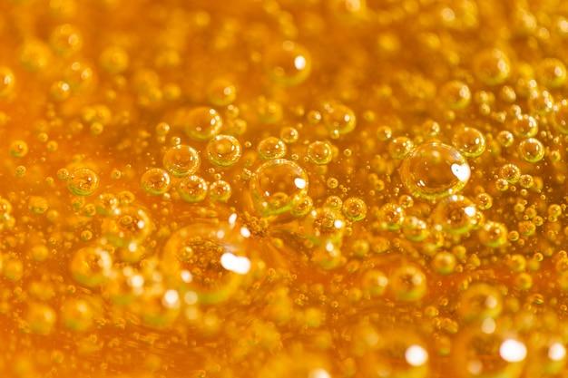 抽象的なオレンジ色の泡の詳細は、背景に使用できます。砂糖漬けのクローズアップ用のペースト。脱毛と脱毛のコンセプト。マクロ写真。