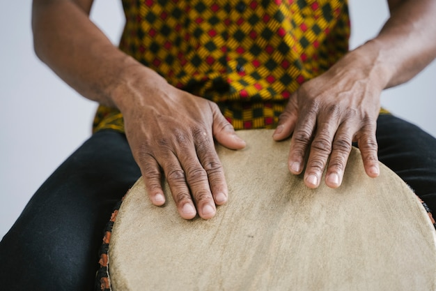 自宅で伝統的なドラムを演奏するアフリカ系アメリカ人の音楽家の詳細。オンライン音楽クラスのコンセプト。レジャー学習楽器。リズムとブルースのスタイル。民族の多文化の伝統。
