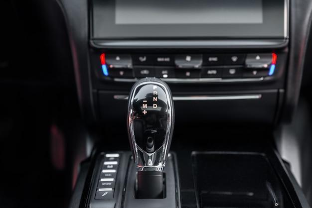 Деталь автоматического переключения передач в новом современном автомобиле. детали интерьера кабины. интерьер автомобиля с крупным планом автоматической коробки передач.