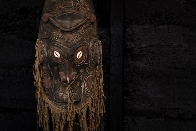 검정색 배경에 나무로 만든 오래된 의식 마스크의 세부 사항. 의식 속성. 복사 공간