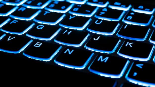 ノートブックキーボードの青いイルミネーションの詳細。技術コンセプト。セレクティブフォーカス。
