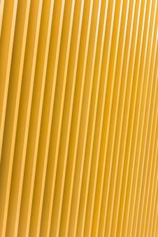 明るい黄色の金属の建物のファサードの詳細。背景について