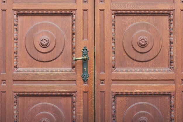 Деталь коричневой резной входной двойной двери, крупный план дверной ручки.