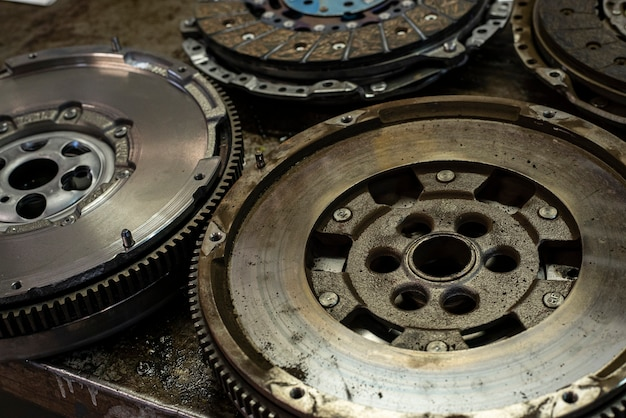 Деталь автомобильного маховика в мастерской, автозапчасти старые и новые