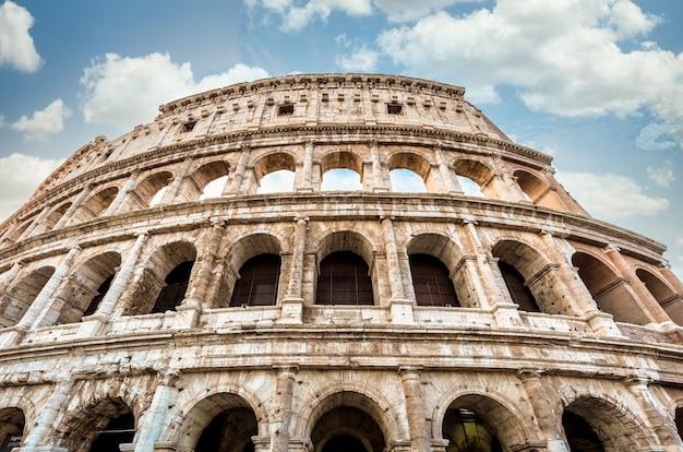 Деталь колизея в риме (рома), италия. также называемый колизеем, это самая известная достопримечательность италии. эффектное голубое небо в фоновом режиме.