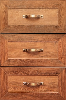 장식 된 가구 서랍의 세부 사항. 오래된 서랍-댐퍼. 청동 캐비닛 하드웨어 서랍이있는 고품질 오크 나무 캐비닛의 클로즈업 세부 사항