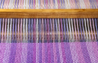 Detail of fabric in comb loom with ultraviolet and lilac colors