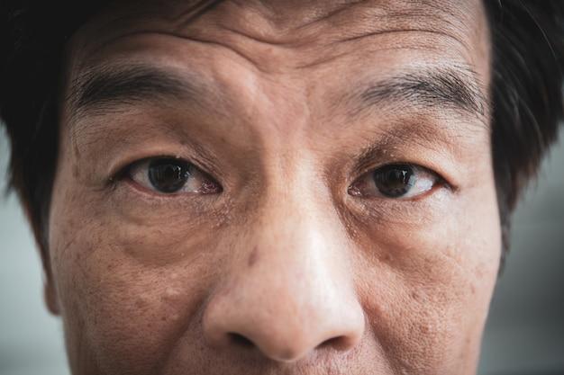 アジアの老人の顔の細部をクローズアップ。ヴィンテージ色のトーンで処理されます。